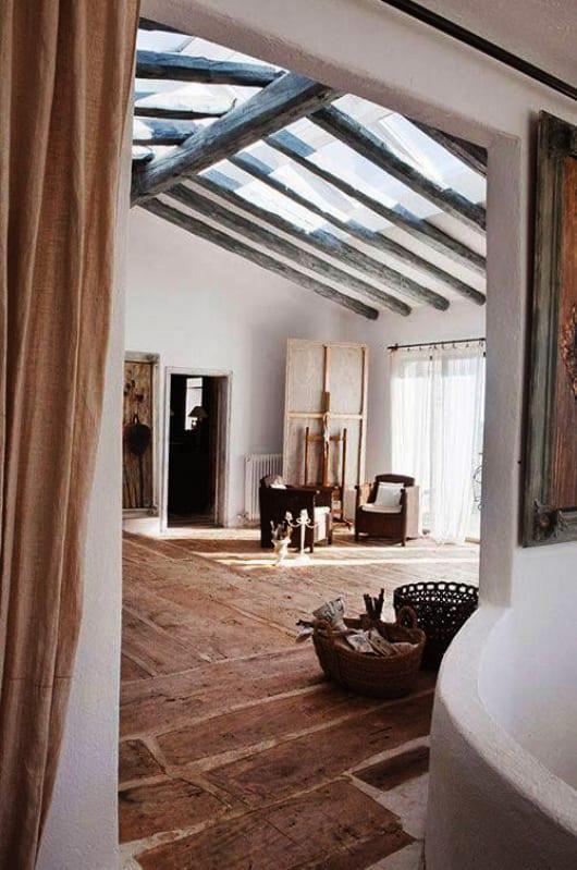 modernes haus im mediterranen wohnstil mit raumtrennung durch gardinen in beige und rustikalem bodenbelag aus holzbrettern in beton