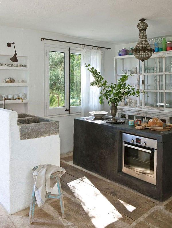 mediterranes haus mit rustikaler kücheneinrichtung mit kochinsel aus beton und Küchenspüle aus Naturstein