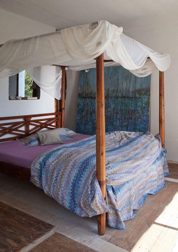 modernes haus und mediterrane schlafzimmer einrichtung mit himmelbett aus holz und bettwäsche in lila und blau