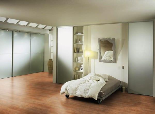 modernes schlafzimmer mit holzboden und eingebauten Kleiderschränken mit beleuchtung und spiegel als kreative wandgestaltung über dem bett im schlafzimmer