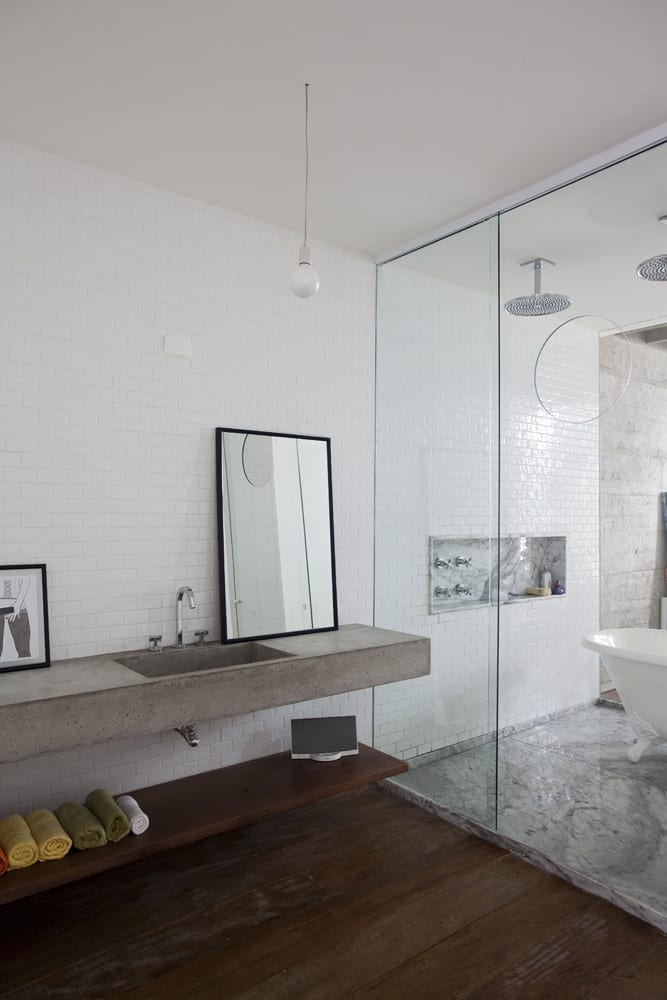modernes Schlafzimmer mit Badezimmer in Loft Wohnung_moderne Badezimmer mit Waschtisch aus Beton und Duschkabine aus Glas mit freistehender badewanne