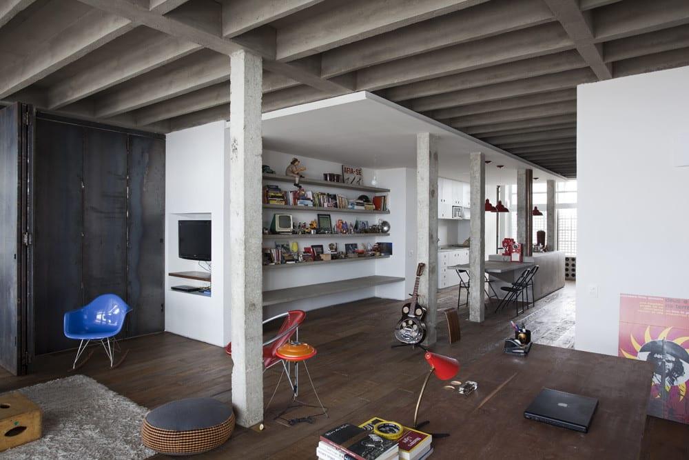 Copa Apartment und Loft Wohnung mit Holzbodenbelag und sichtbaren Deckenbalcken aus Beton_modernes Wohnzimmer Design mit grauen Bücherregalen und Designer Stühlen in blau und rot