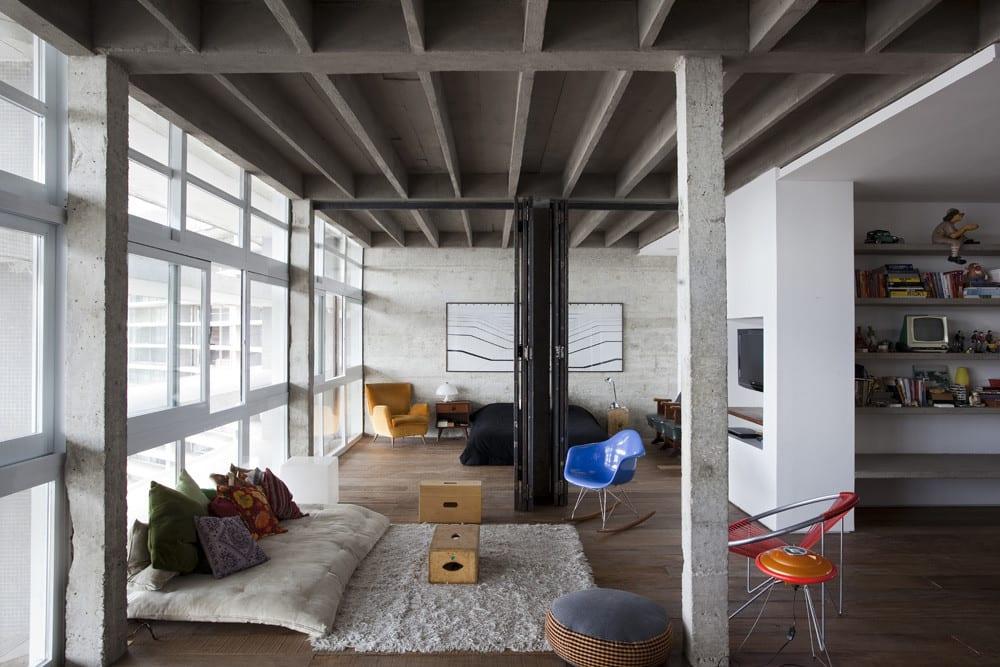 modernes Wohnzimmer Design einer Loft Wohnung aus Beton mit Luxus Sxhlafzimmer und Falttüren als Raumteiler