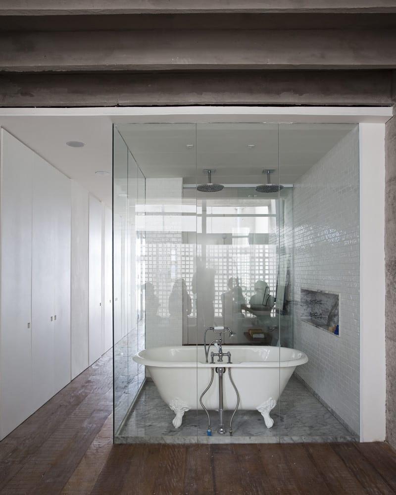 Apartment mit modernem Badezimmer und Dusche mit Glaswänden und Badewanne freistehend