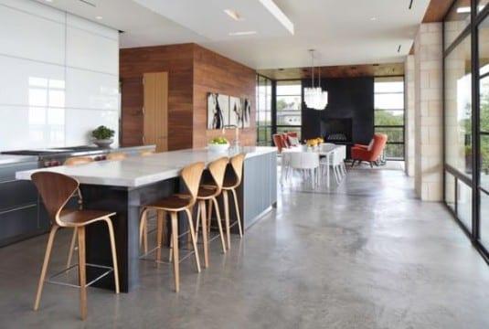 schönes wohnzimmer design mit betonboden und moderne küche weiß mit Kochinsel und bar mit Barhockern aus holz