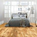 kleines schlafzimmer einrichten und gemütlich gestalten mit Parkettbodenbelag und moderne Stehlampe aus holz