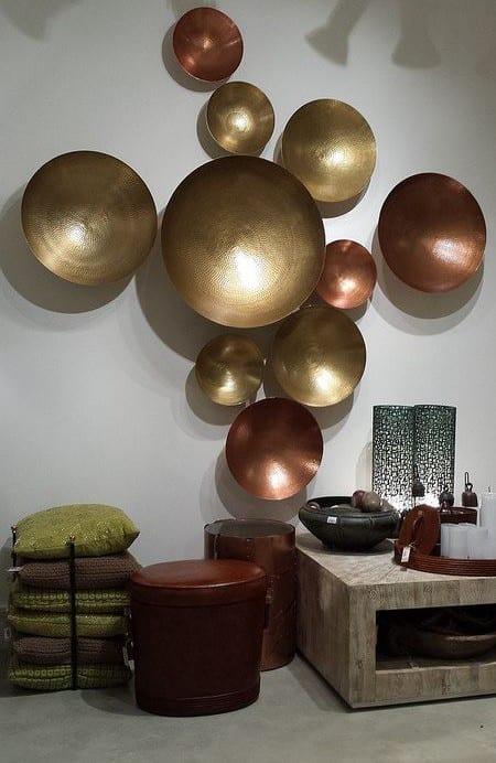moderne wandgestaltung mit runden metallschalen aus bronze und coole dekoideen wohnzimmer mir dekokissen in grün und designer deko-accessoires