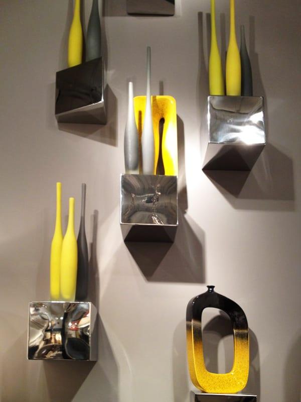 wohnzimmer wandgestaltung mit wandfarbe grau und silbernen regalen mit gelben vasen
