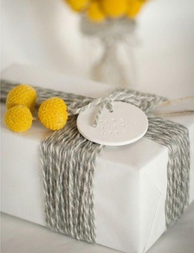 geschenk kreativ verpacken mit frischen blumen gelb und graue fäden