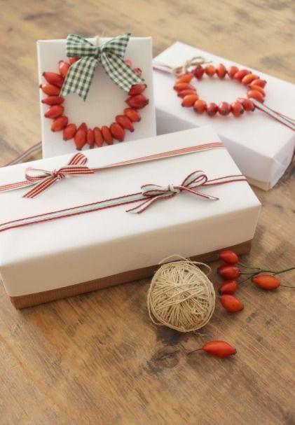 geschenk schön verpacken mit weißem geschenkpapier und diy deko aus hagebutten