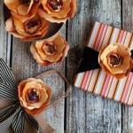 geschenke kreativ verpacken mit orangen papierblumen und schwarzer band