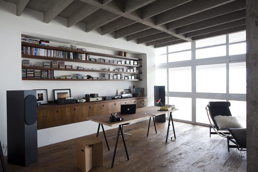 Apartment minimalistisch einrichten mit Home Office im Wohnzimmer mit eingebautem Büroschrank und Designer Lige aus schwarzem Leder