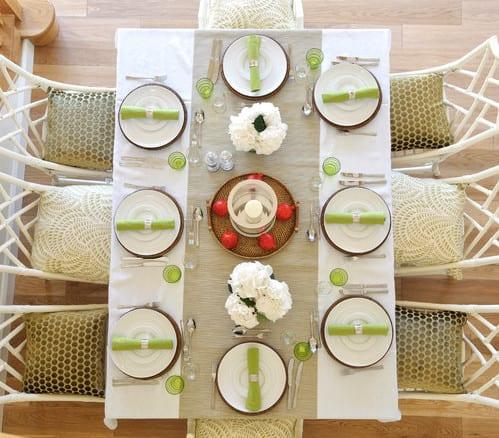 tisch eindecken in weiß und grün und esstischstühlen weiß aus holz mit grünen sitzkissen dekorieren