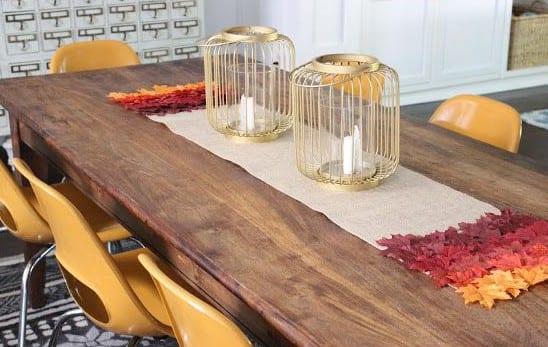herbstdeko idee und tischdeko idee mit goldenen metall-laternen und diy tischläufer aus rupfen und baumblättern
