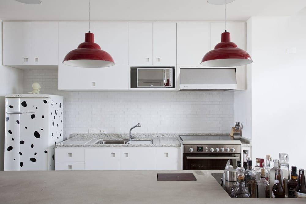 moderne Küche weiß mit Kochinsel aus beton und Pendellampen rot als Akzent zu den weißen eingebauten Küchenschränke