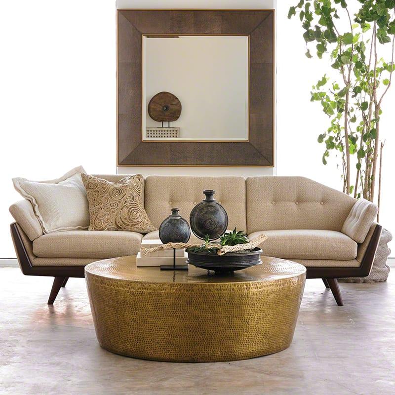 modernes wohnzimmer gestalten mit rundem coychtisch aus messing und Designer sofa beige und kreative wandgestaltung mit Holzspiegelrahme