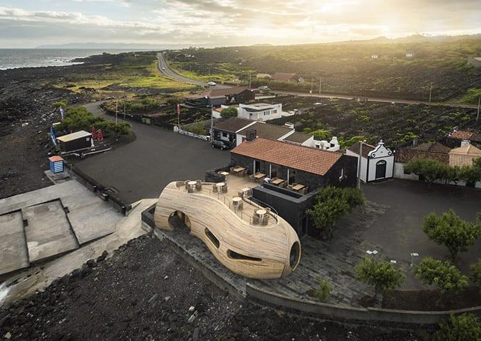 moderne architektur und moderner holzbau mit runden formen als erweiterung einer steinhütte