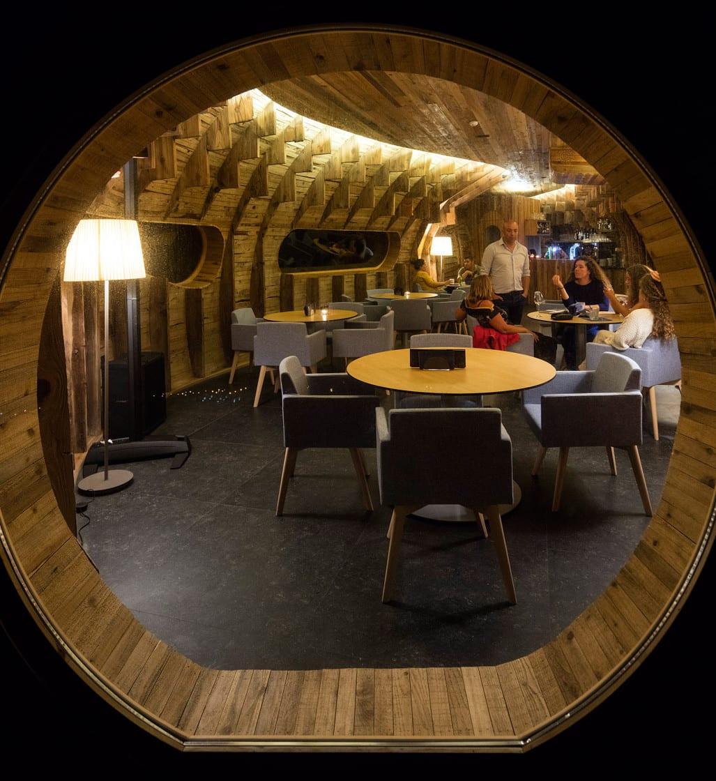 restaurant bar mit rundfenster und runden holztischen und armsesseln in blau
