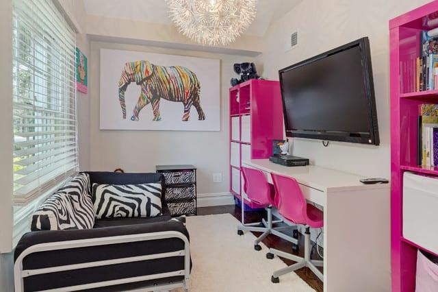 kleines kinderzimmer für mödchen mit sofa schwarz und Ikea-regalen in pink einrichten