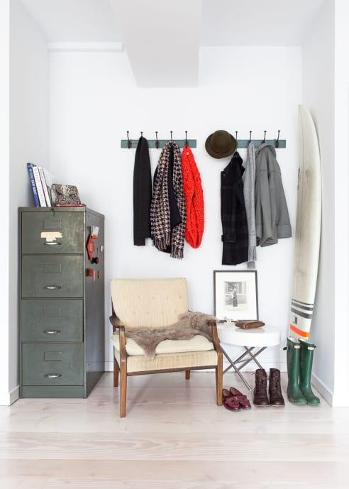 kleiner eingangsbereich gestalten mit sessel und grauen Metallschrank und Kleiderhacken für die wand