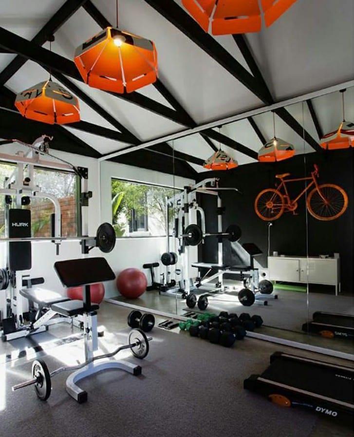 farbgestaltung in schwarz weiß mit orangen pendellampen und wanddeko idee mit fahrrad