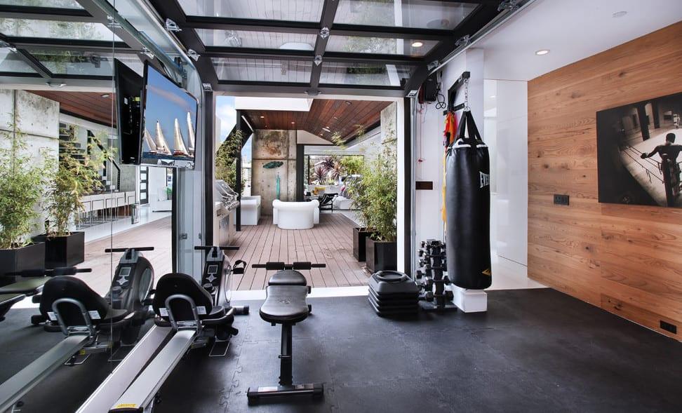 moderner fitnessraum einrichten mit tv-wandpaneel aus holz und dachverglasung