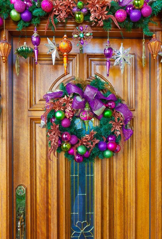 moderne haustür holz mit fenster zu weihnachtszeit dekorieren mit Weihnachtsbaumkugeln und Weihnachtstürkranz