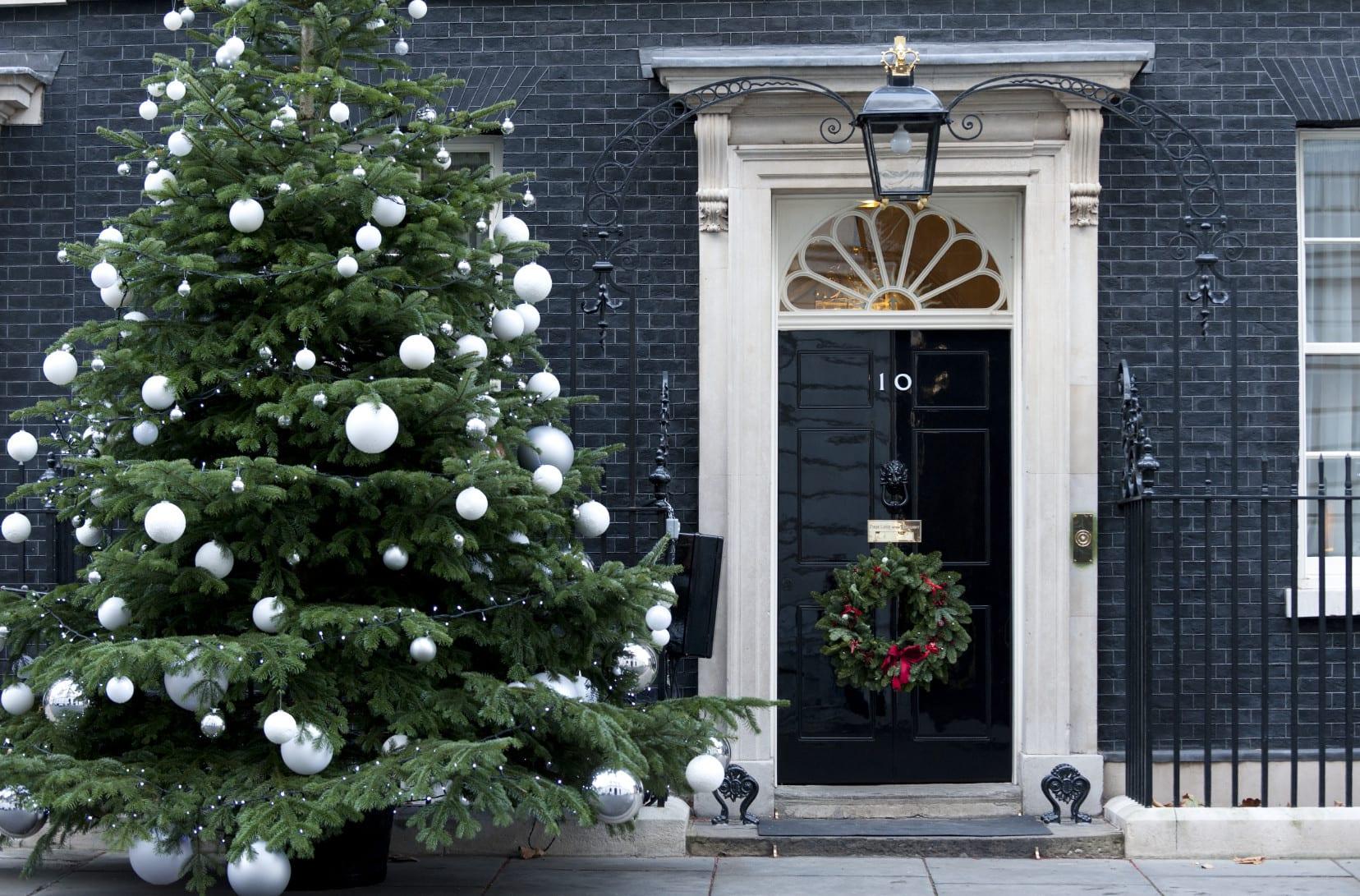 modernes haus mit außenwand aus schwarzen ziegeln mit haustür in schwarz lackfarbe eihnachtlich dekorieren mit Weihnachtsbaum und türkranz