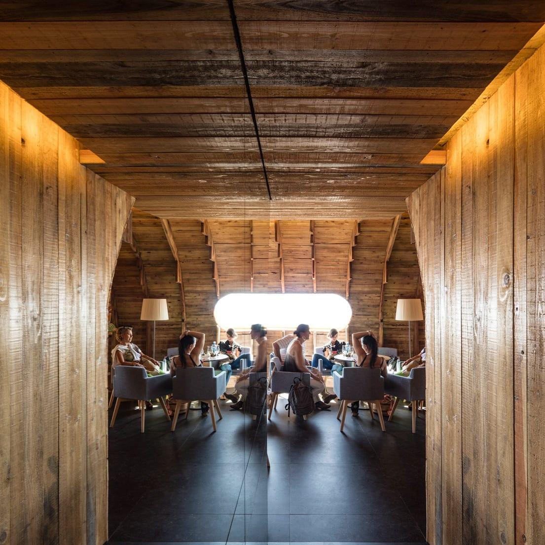 bauen mit holz als beispiel für modernes restaurant bar-interieur mit holwänden und indirekter deckenbeleuchtung über aufgehänter holzdecke