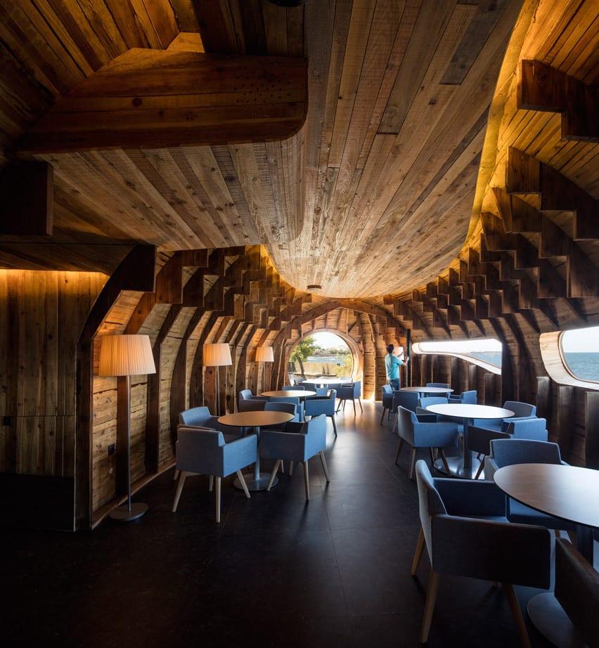 bauen mit holz als beispiel für modernes interioir mit holzdecke und gerundeten holzwänden_modernes restaurant bar mit stehlampen und runden holzesstischen mit blauen armstühlen