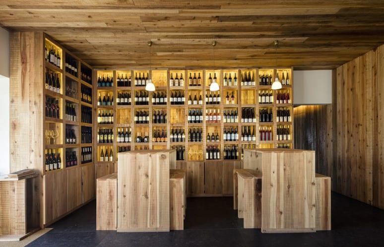 bauen mit holz_holz interieur und einrichtungsidee für weinkeller mit weinregalen aus Holz und rechteckige Bartische mit Sitzbänken aus holz