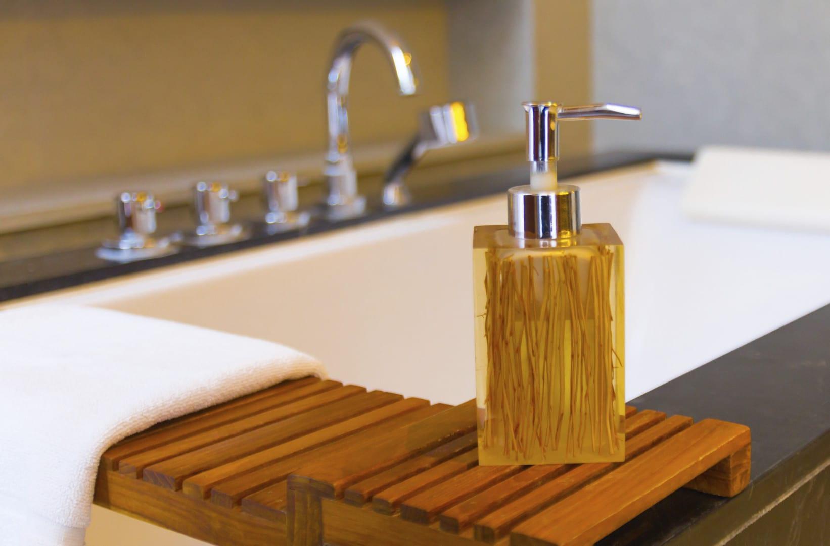 schöner wohnen badezimmer_badewanne mit natursteinverkleidung in schwarz und moderne badezimmer-accessoires