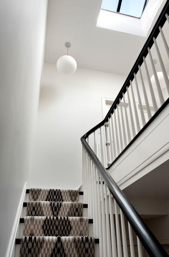 treppenraum interieur mit innentreppe weiß und geländer schwarz