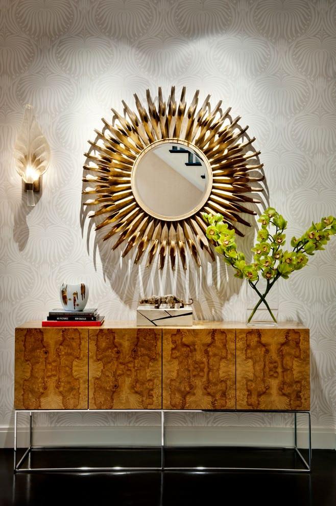 zimmer einrichten mit designer sideboard holz und wandlampe neben rundem spoegel mit metallrahmen gold