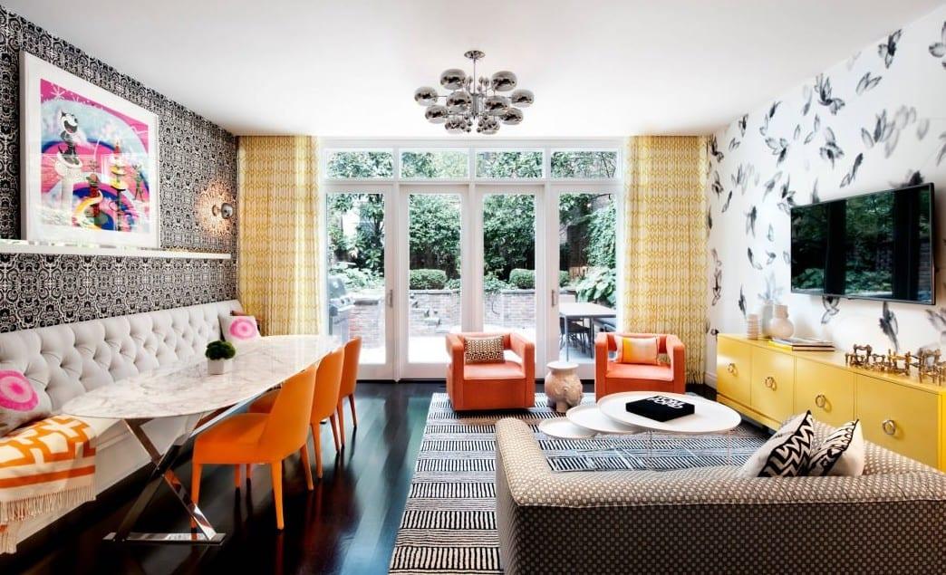 modernes wohnzimmer mit weißem sofa-bank und esstisch oval weiß mit orangen stühlen und polstersesseln und teppich mit streifenmuster in schwarzweiß