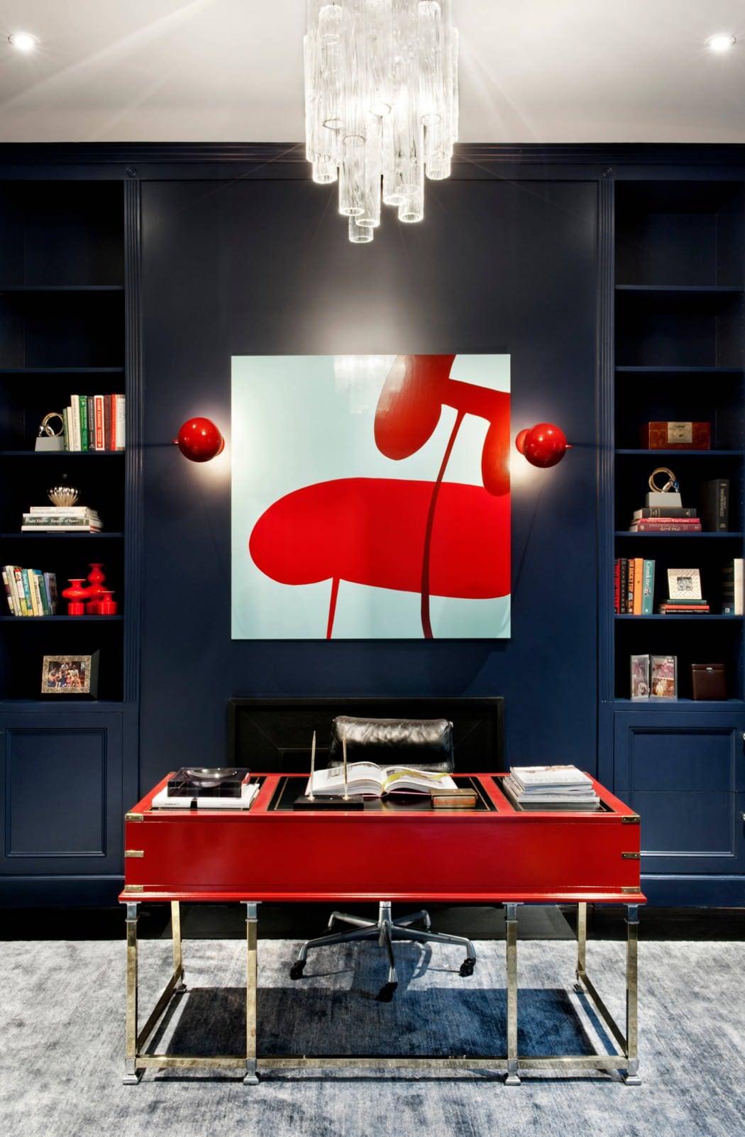 interieur in blau und rot mit eingebaiten Regalen blau und kamin schwarz hinter rotem schreibtisch