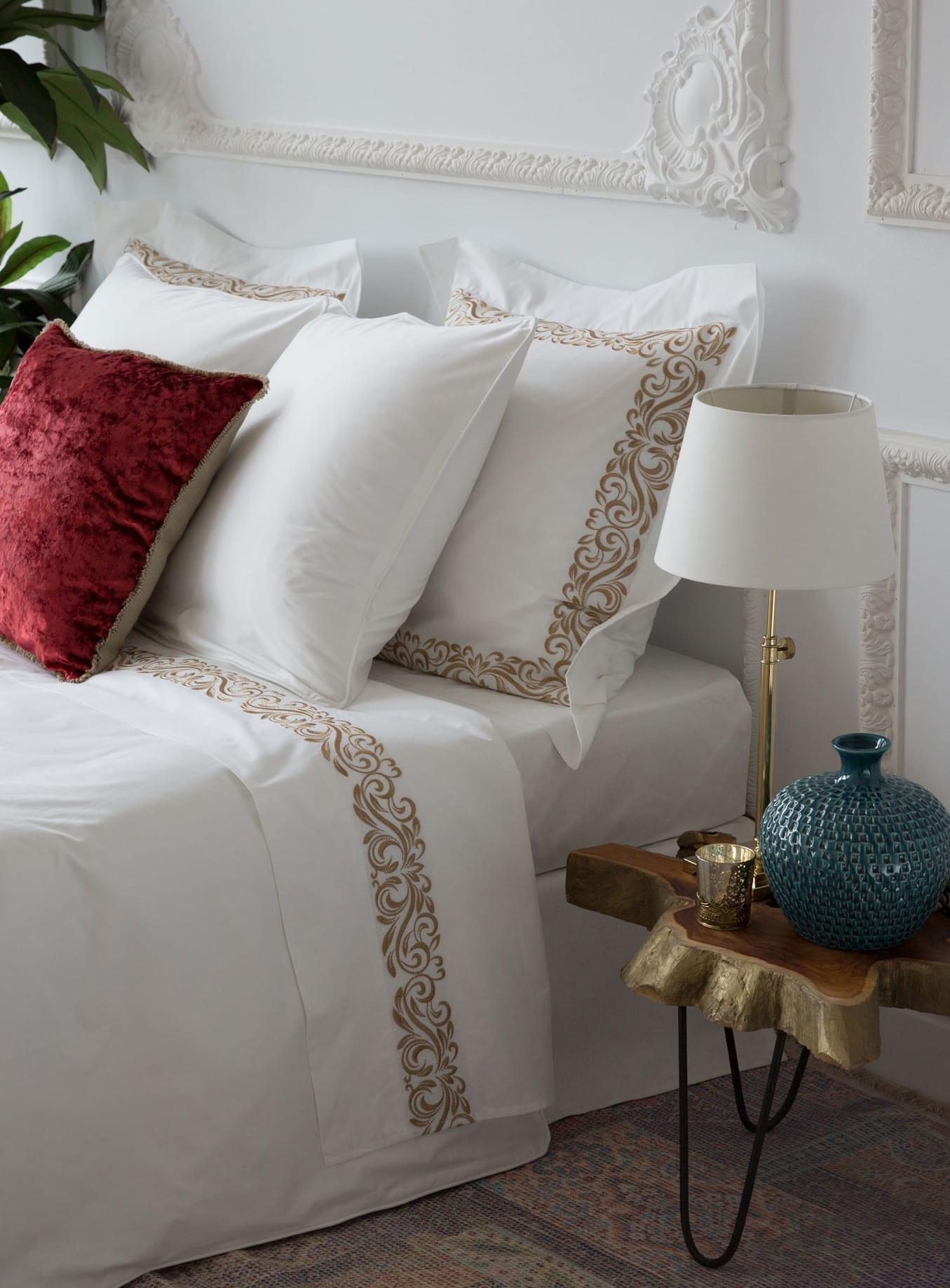 moderne schlafzimmer einrichten mit zara home kissen und bettwäsche weiß und gold und designer-nachttisch aus holz