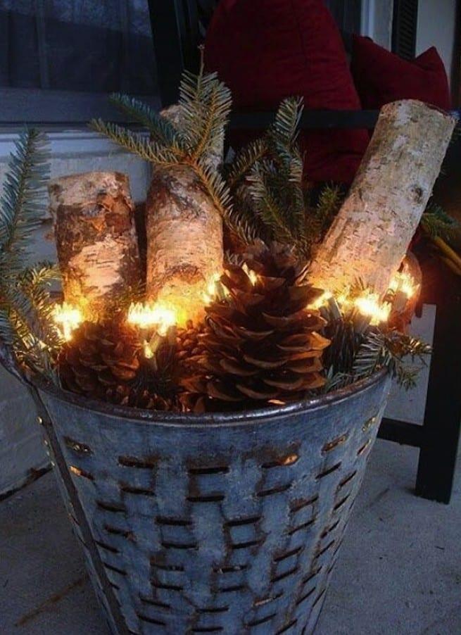 weihnachtsdeko aussen mit rundhölzern und lichtkette