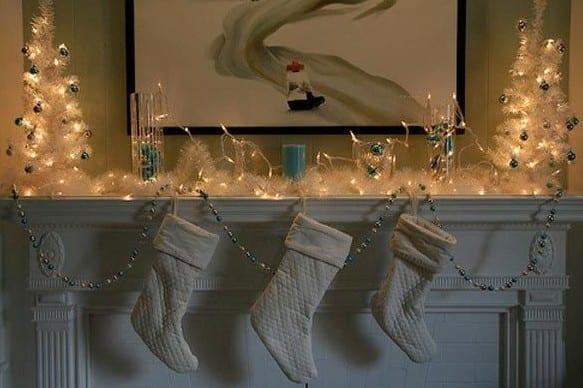 weißer kamin weihnachtlich dekorieren mit lichtkette und weihnachtsdekoration weiß