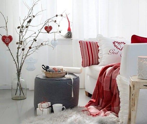 kleines wohnzimmer weihnachtlich dekorieren mit getrockneten zweigen und roten decke und kissen für polstersessel weiß