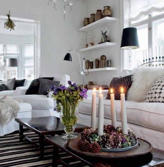 kleines wohnzimmer weiß weihnachtlich dekorieren mit lilafarbigen blumen und tischdeko weihnachten mit zapfen und kranz mit kerzen
