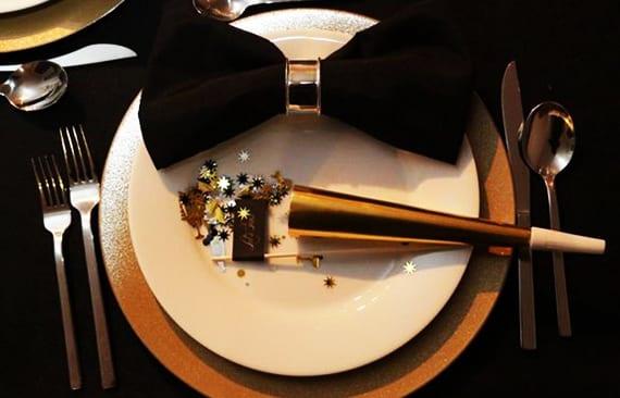 festliche tischdeko in gold und schwarz mit fliege-servietten