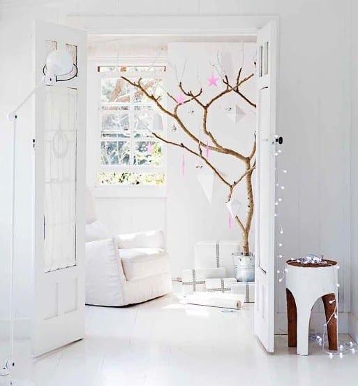moderne weihnachtsdekoration in weiß mit diy-weihnachtsbaum aus ästen mit rosafarbigen sternen als weihnachtsbaum-schmuck
