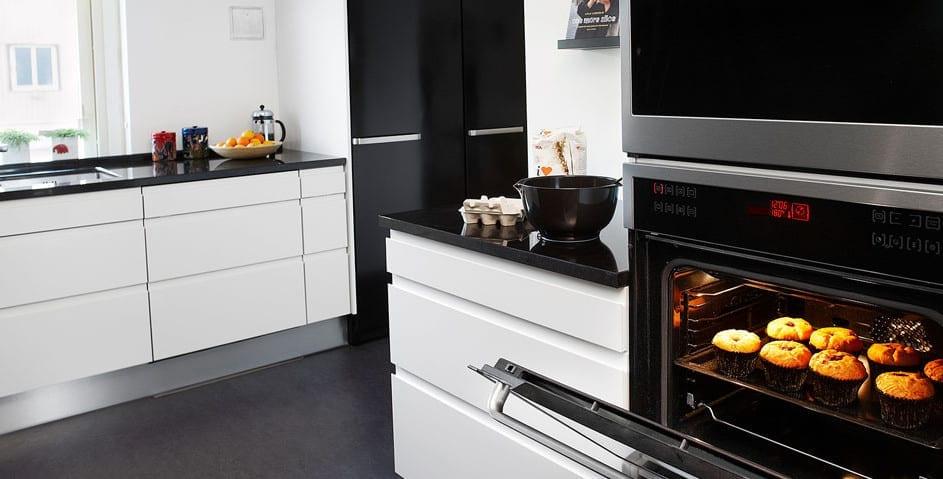 kleine küche weiß mit weißen küchenunterschränken mit schubladen und küchenarbeitsplatte aus granit schwarz_moderne küche in schwarz-weiß einrichten und mit eingebautem bachofen ausstatten