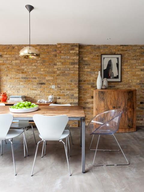 moderne küche im industrial chic style mit ziegelwand und fließestrichboden_eszimmer einrichten mit esstisch holz und weißen esszimmerstühlen und pendellampe gold