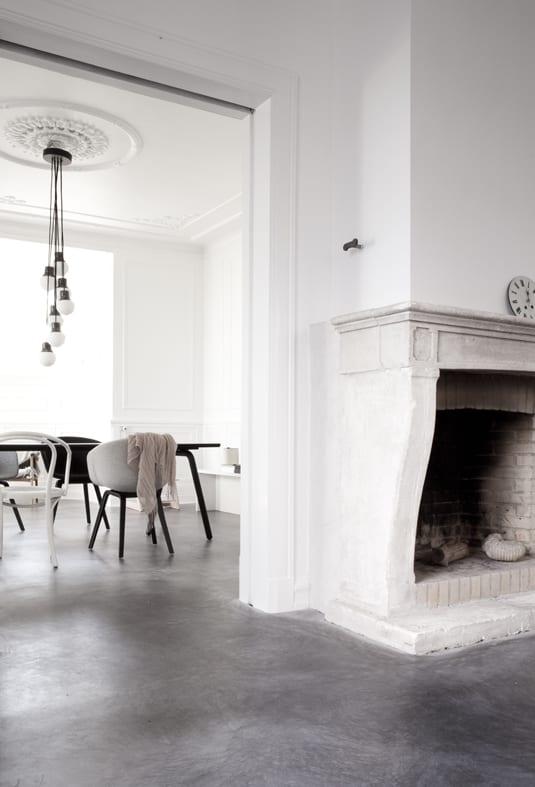 minimalistische wohneinrichtung mit weißen wänden und estrichboden im dunkelgrau