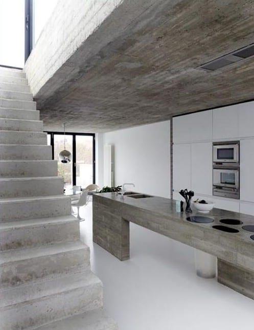 minimalistische küche weiß mit weißen küchenschränken eingebaut und kochinsel aus beton auf estrichboden weiß