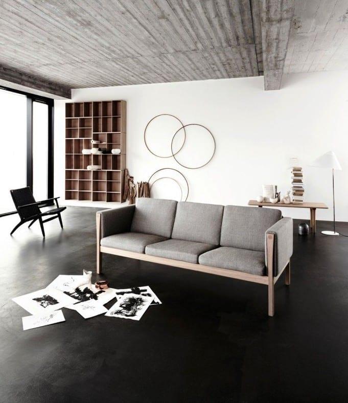 minimalistisches wohnzimmer design mit schwarzem estrich als bodenbelag und designer-sofa grau mit kreativer wandgestaltung mit holzwandregal und holzernen kreisen