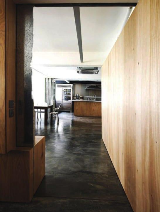 moderne küche im industrial chic style mit schwarzem estrichboden und holzwandverkleidung im flur und in der küche mit kochinsel aus holz