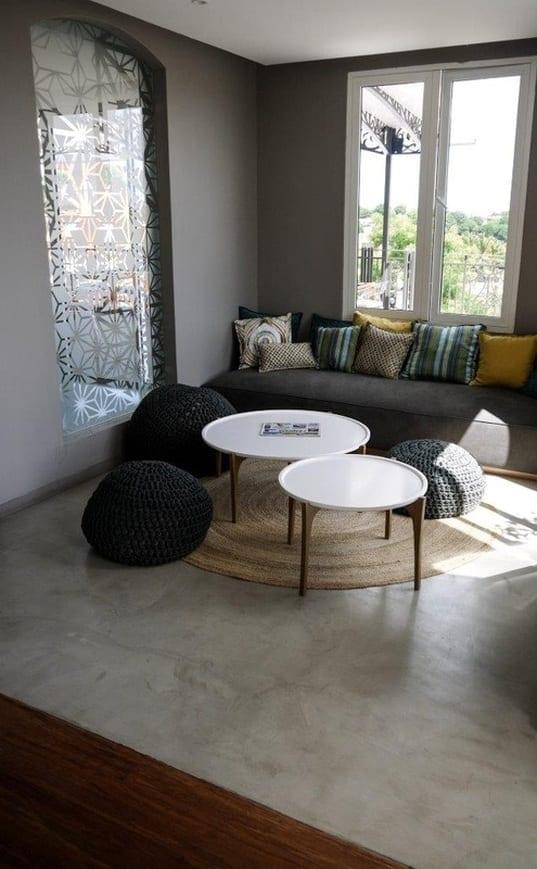 kleines wohnzimmer modern gestalten mit wandfarbe grau und runden couchtischen und schwarzen polsterhockern